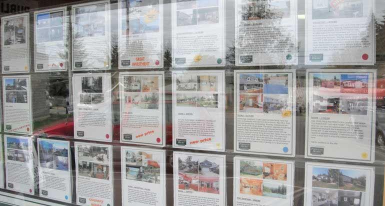 Escaparate con anuncios para poder vender con una agencia inmobiliaria