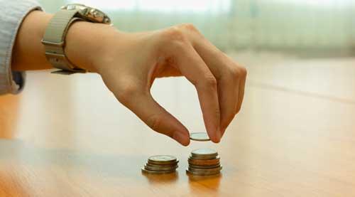 Mano cogiendo monedas para ilustrar el artículo requisitos para pedir una hipoteca